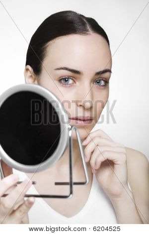 Young Attractive Woman Looks Over A Mirror