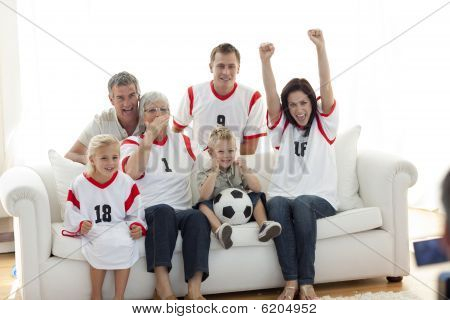 Happy Family Watching A Football Match In Television