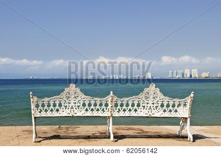 White metal bench on Malecon at Pacific ocean in Puerto Vallarta, Mexico