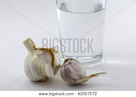 Glass Of Water And Some Garlic Isolated On White Background