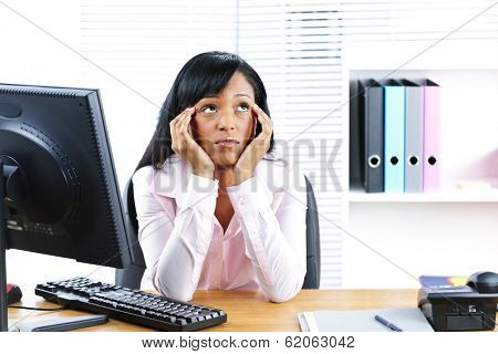 Bored unhappy young black business woman at desk in office