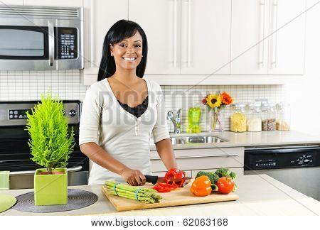 Smiling black woman cutting vegetables in modern kitchen interior