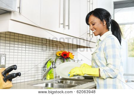 Smiling young black woman washing dishes in kitchen