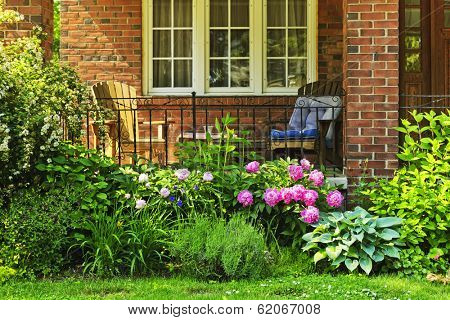 Front of home with chairs and flower garden
