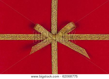 Red present wrapped with gold ribbon and bow