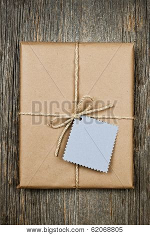 Gift package and card in brown paper wrapper tied with string on rustic wood background