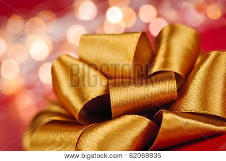 Golden ribbon gift bow closeup with festive lights