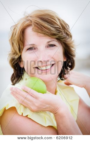 Beautiful mature woman holding an apple
