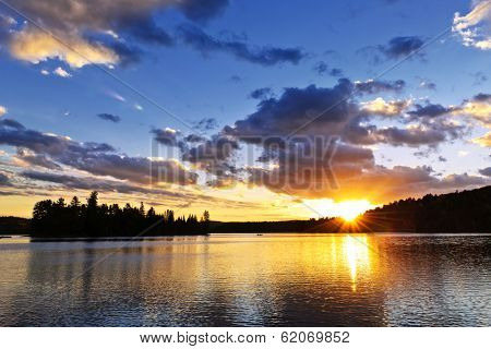 Sun setting over tranquil lake and forest in Algonquin Park, Canada