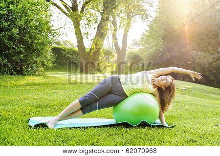 Female fitness instructor using yoga exercise ball  outdoors in morning sunshine