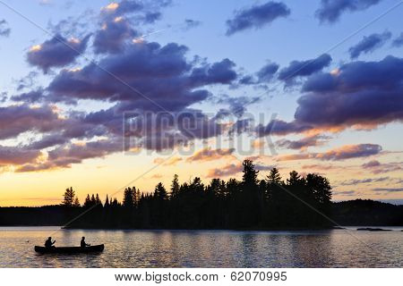 Silhouette of island and canoe on lake at sunset in Algonquin Park, Canada