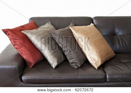 Four colorful cushions on dark brown leather couch