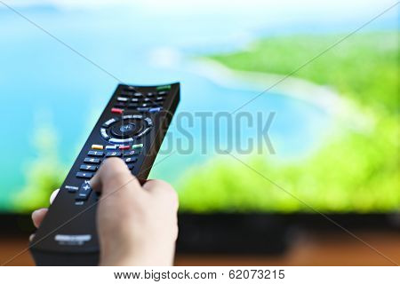 Hand holding television remote control pressing buttons