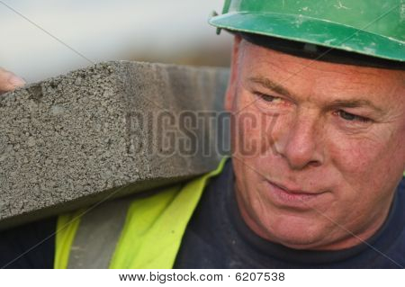 Bricklayer Lifting Breezeblock On Construction Site