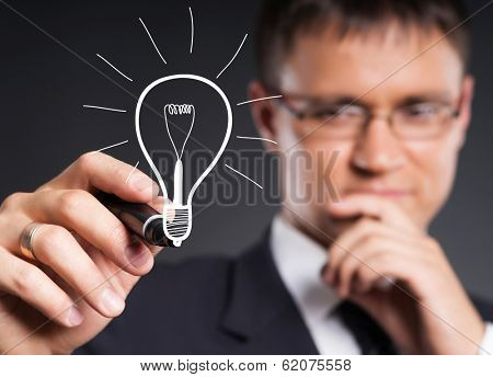 Businessman working with a lamp bulb. Idea and eureka concept.