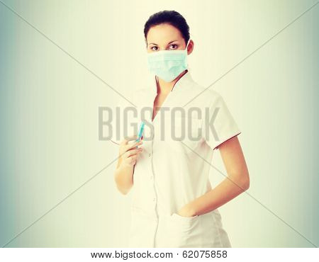 Young nurse in mask with syringe,  over gray background