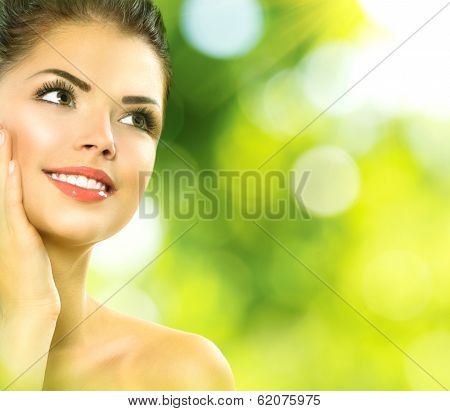 Beauty Spa Woman over nature green background. Spring. Beautiful Girl Touching her Face. Perfect Fresh Skin. Pure Beauty Model Girl. Healthy smile. Health Care concept. Natural cosmetics