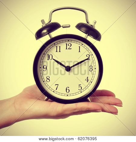 a woman holding a typical mechanical alarm clock on a beige background, with a retro effect