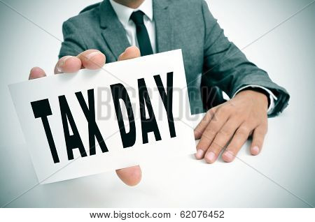 a businessman sitting in a desk showing a signboard with the text tax day written in it