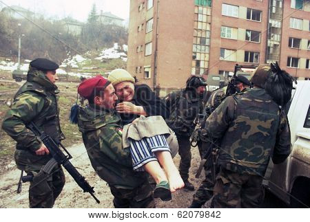 SARAJEVO, BOSNIA - MAR 18: Italian army troops, in Bosnia as part of the United Nation's  UNPROFOR, help an injured woman to safety in Sarajevo, Bosnia, on Monday, March 18, 1996.