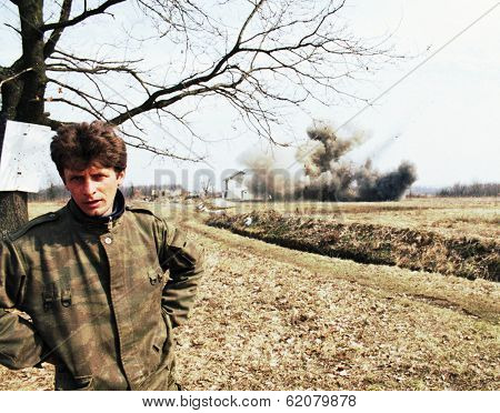 ODZAK, BOSNIA - MAR 24: A Bosnian Serb soldier talks while his house is blown up by United States Army troops in Bosnia as part of NATO's IFOR,  near Odzak, Bosnia, on Sunday, March 24, 1996. The house contained explosives