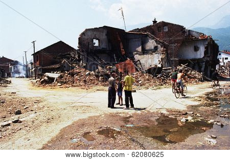 PEC, KOSOVO - JULY 3: Returning  refugees survey the destroyed downtown of Pec, Kosovo, on Saturday, July 3, 1999.  Much of Kosovo was destroyed during fighting with Serb forces.