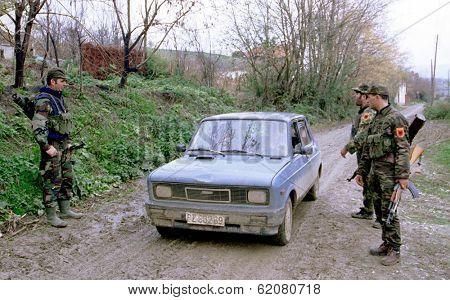 RETMILJE, KOSOVO,  12 NOVEMBER 1998 --- Soldiers of the Kosovo Liberation Army (KLA) stop a car at a makeshift roadblock in the Drenica Triangle.