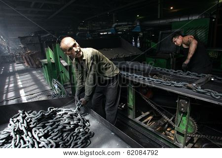 DONETSK - JULY 13: Steel workers create linked chain at the CJSC Vistec steelworks in Donetsk, Ukraine,  on Thursday, July 13, 2006.