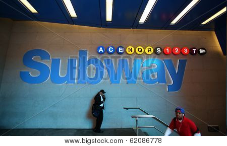 NEW YORK CITY - OCT 17:  Pedestrians walk past the entrance to a New York City subway station in Manhattan on Thursday, October 17, 2013.