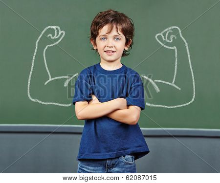 Strong child with muscles drawn on chalkboard in elementary school