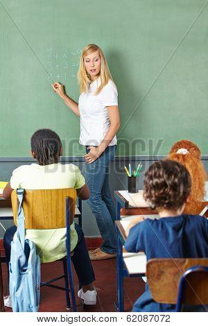 Teacher writing on chalkboard in math class in elementary school