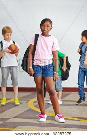 African girl standing with knapsack on schoolyard in elementary school
