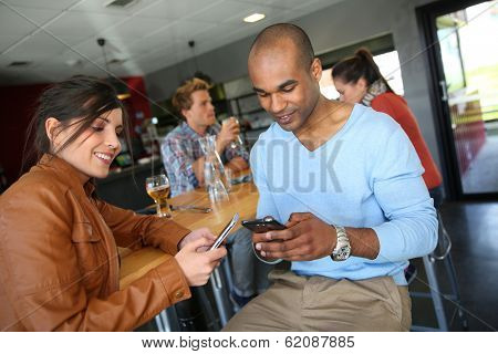 Young people in coffee shop using smartphones