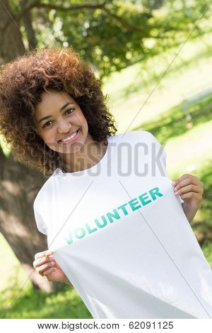 Portrait of smiling environmentalist holding volunteer tshirt in park