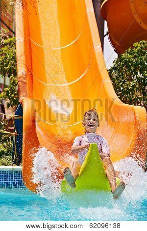 Child on water slide at aquapark. Summer holiday.
