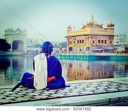 Vintage retro hipster style travel image of unidentifiable Seekh Nihang warrior meditating at Sikh temple Harmandir Sahib. Amritsar, India