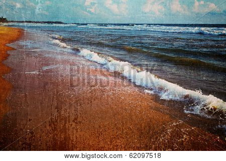 Vintage retro hipster style travel image of wave surging on sand on beach with grunge texture overlaid