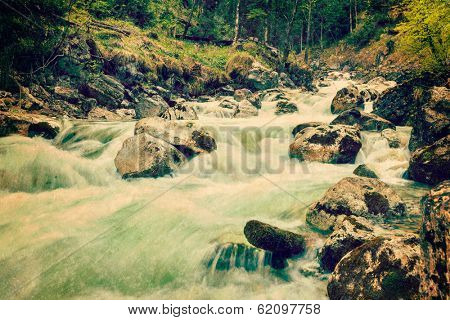 Vintage retro hipster style travel image of cascade of Kuhfluchtwasserfall. Long exposure for motion blur. Farchant, Garmisch-Partenkirchen, Bavaria, Germany