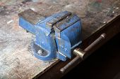 image of work bench  - old blue battered bench vice on work bench - JPG