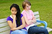 Two bored teenage girls sitting on bench