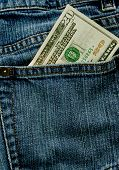 foto of twenty dollars  - A twenty dollar bill sticking out the back pocket of denim blue jeans - JPG