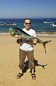 picture of mahi  - Happy tourist holding his big fish catch after fishing trip in Mexico - JPG