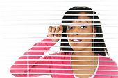 Young black woman looking through horizontal venetian blinds