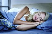 stock photo of laying-in-bed  - Young woman sleeping peacefully at night in bed - JPG