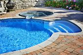 Outdoor in ground residential swimming pool in backyard with hot tub