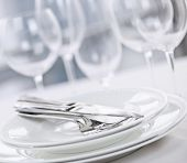 Elegant restaurant table setting with plates cutlery and stemware