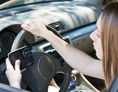 stock photo of illegal  - Teenage girl texting on cell phone while driving - JPG