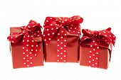 Three presents wrapped in red paper with polkadot ribbon