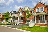 stock photo of row houses  - Suburban residential street with row of red brick houses - JPG