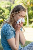 pic of blowing nose  - Side view of a young woman blowing nose with tissue paper at the park - JPG
